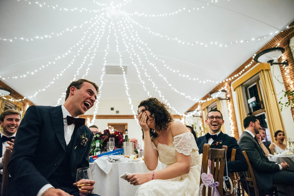 Bride & Groom laugh at speeches at Gothic 80s vintage dress Rotherwick Village Hall DIY Wedding Essex UK Documentary Photographer