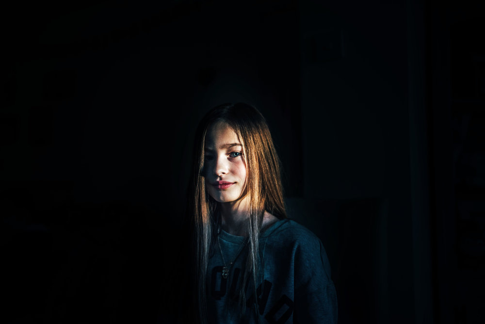 Girl lit by beam of Winter light Essex UK Documentary Photographer