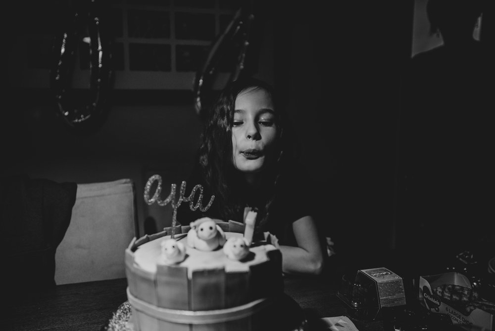 Young girl blows out birthday candles Essex UK Documentary Photographer