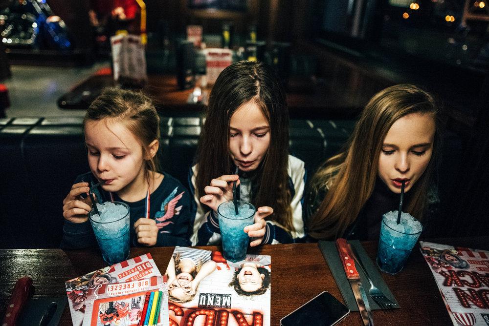 Three girls drink blue drink Essex UK Documentary Photographer