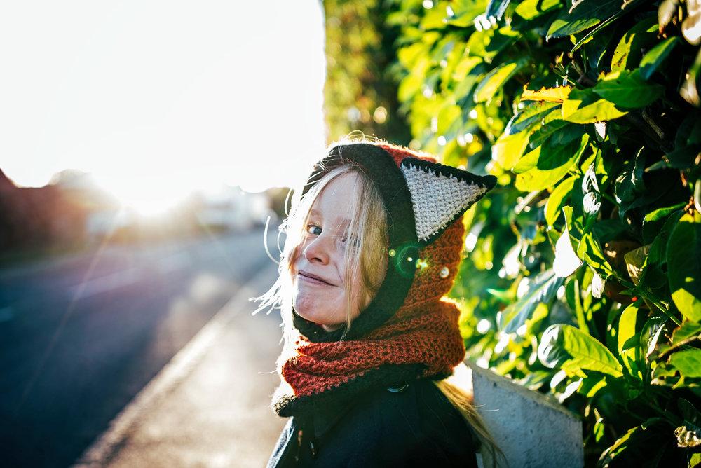 Little girl in fox hat in sun flare Essex UK Documentary Photographer