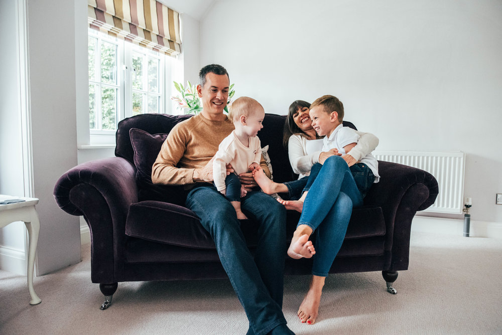 Family laugh on sofa Essex UK Childhood Documentary Lifestyle Photographer