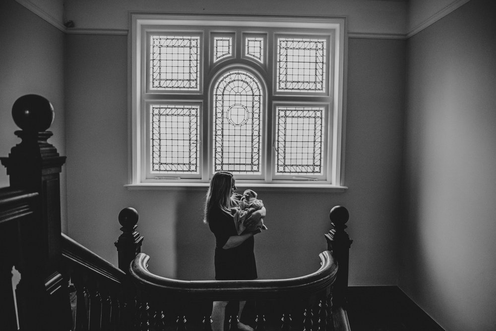 mum cradles new baby on stairwell essex uk documentary lifestyle childhood family photographerw