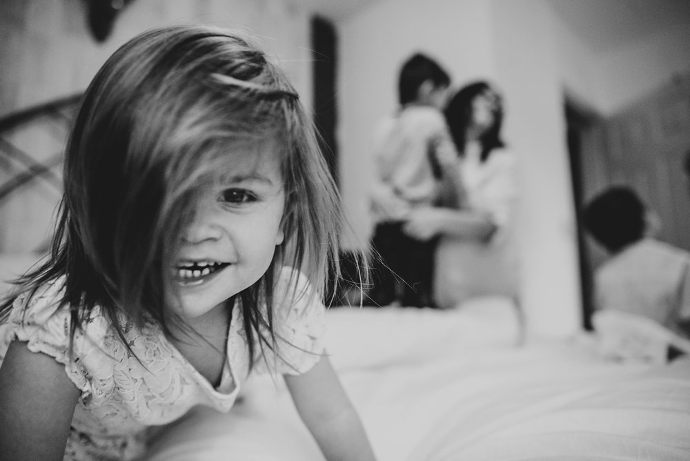 toddler girl laughs on a bed Essex UK family lifestyle childhood documentary photographer