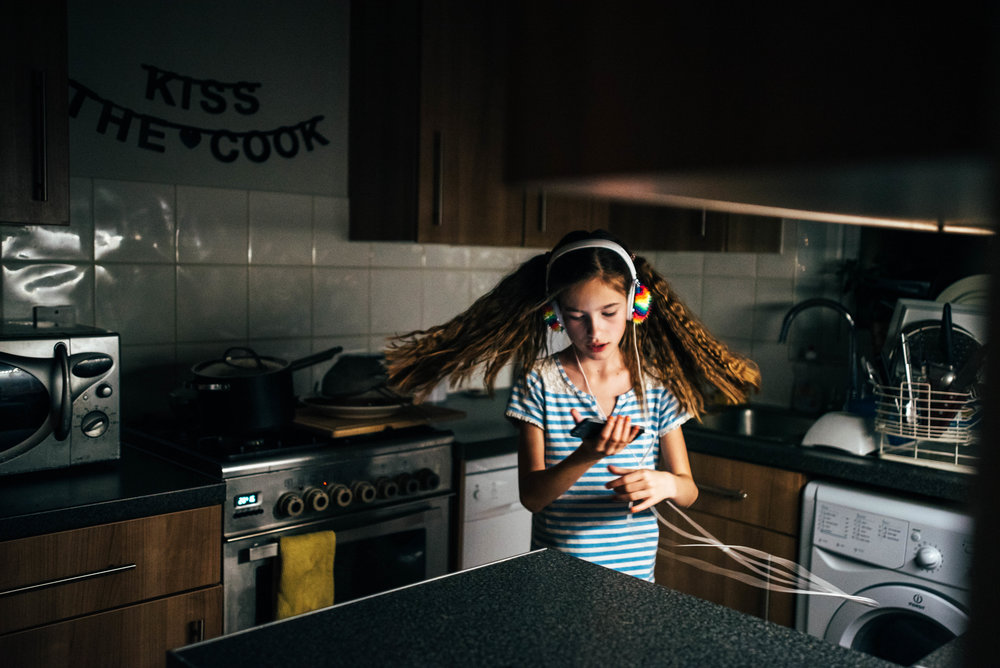 Tween girl dances with headphones in kitchen Essex UK Documentary Portrait Photographer