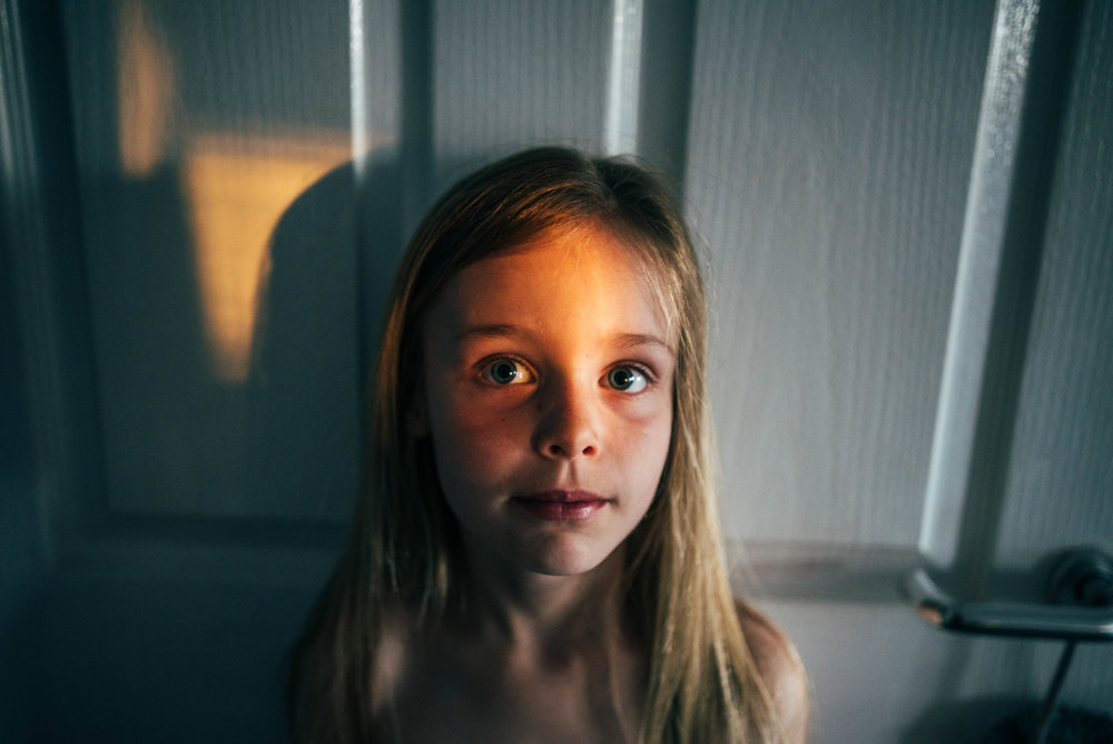 Little girl in pocket of light Essex UK Documentary Lifestyle Portrait Photographer