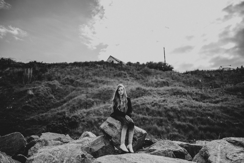Teen girl sits on beach Essex UK Documentary Lifestyle Portrait Photographer