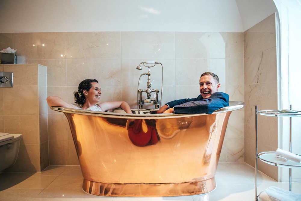 Alternative diy wedding on a boat with steam fairground Essex UK Documentary Wedding Photographer Bride and Groom in copper bath