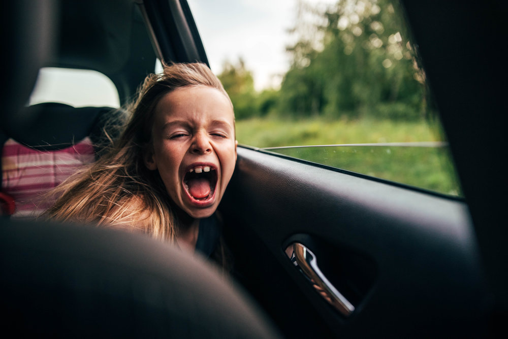 Young girl enjoys breeze in back of car Essex UK Documentary Portrait Photographer
