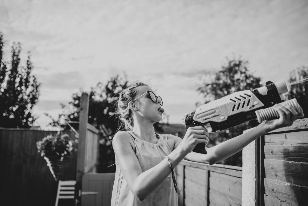 teen girl shoots water pistol over fence Essex UK Documentary Portrait Photographer