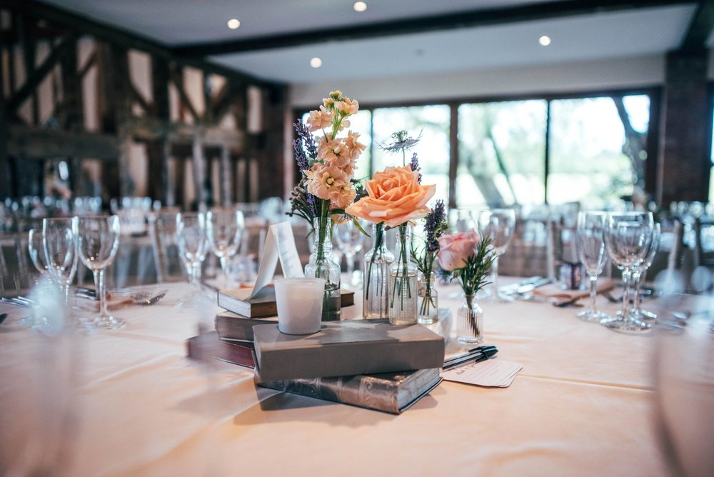 Flowers and Books for centre pieces for Grey & Lilacs Rustic Old Brook Barn Wedding Bride wears Enzoani Essex Documentary Wedding Photographer