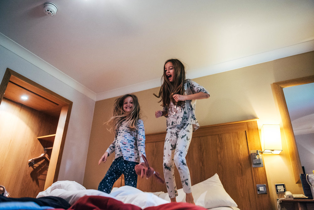 Two girls bounce on bed in hotel Essex UK Documentary Wedding Photographer