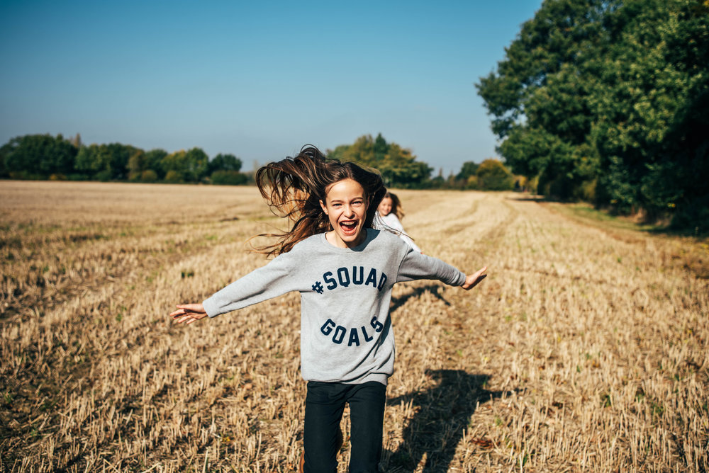 Tween girl running in Autumn field Essex UK Documentary Wedding Photographer