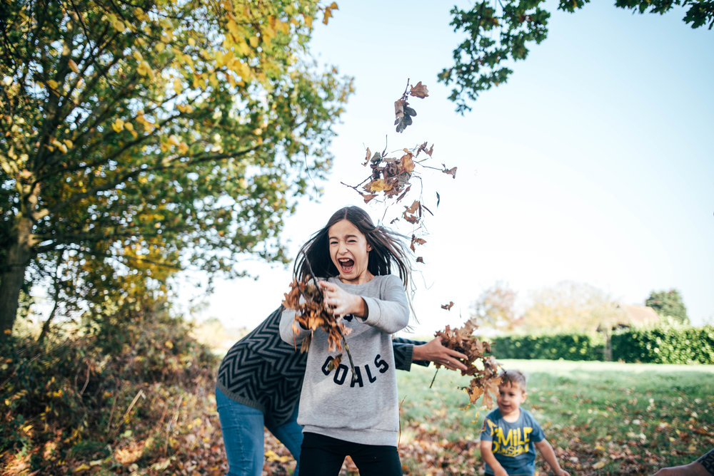 Tween girl throwing autumn leaves Essex UK Documentary Wedding Photographerw