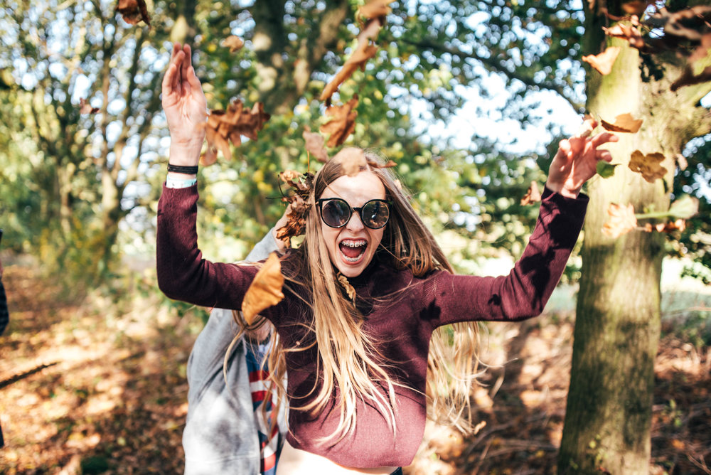 Teen girl throwing autumn leaves Essex UK Documentary Wedding Photographer