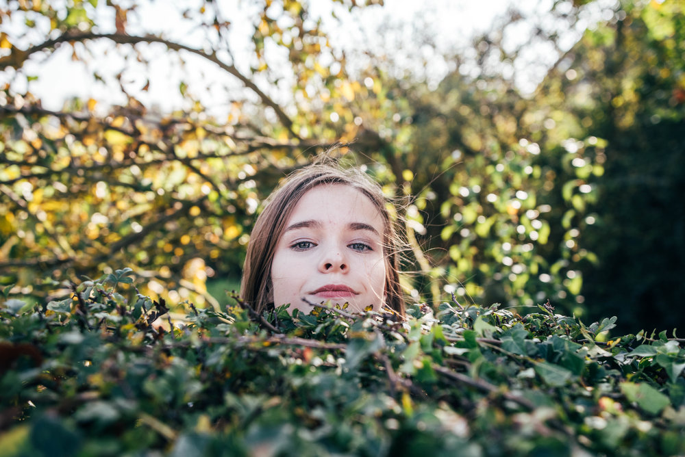 Teen girl peers over hedge Essex UK Documentary Wedding Photographer