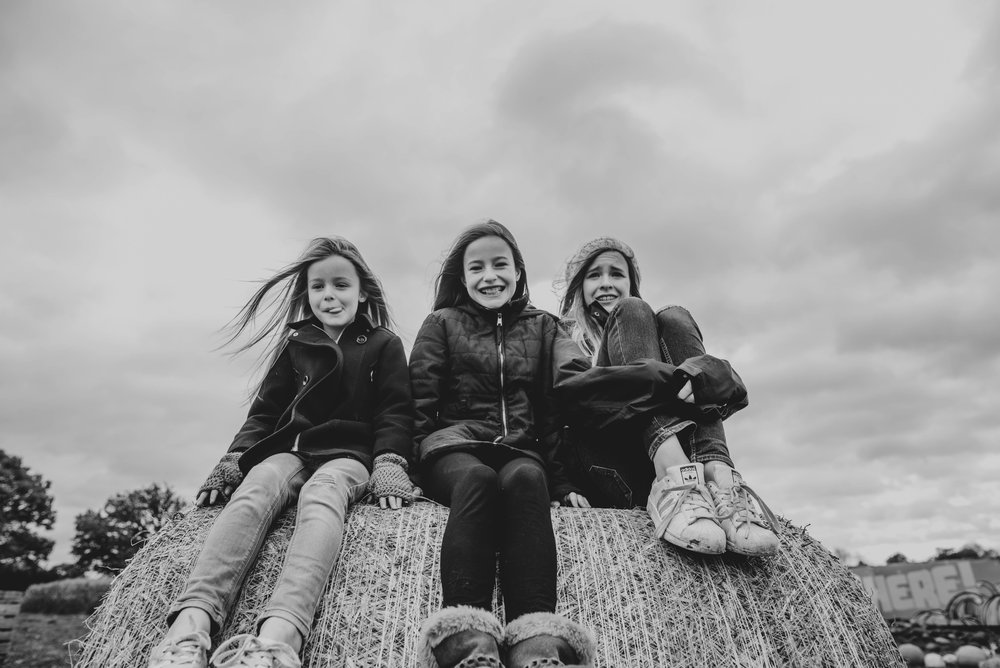 Three sisters sit on hay bale on cold day Essex UK Documentary Wedding Photographer