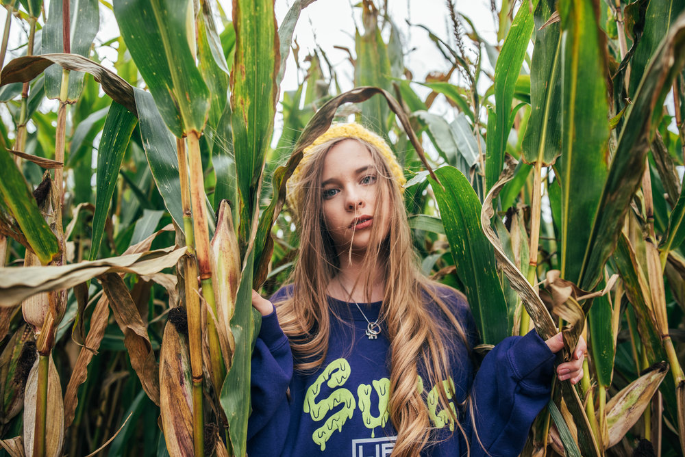 Teen girl in Sugg Life jumper stands in cornfield Essex UK Documentary Wedding Photographer