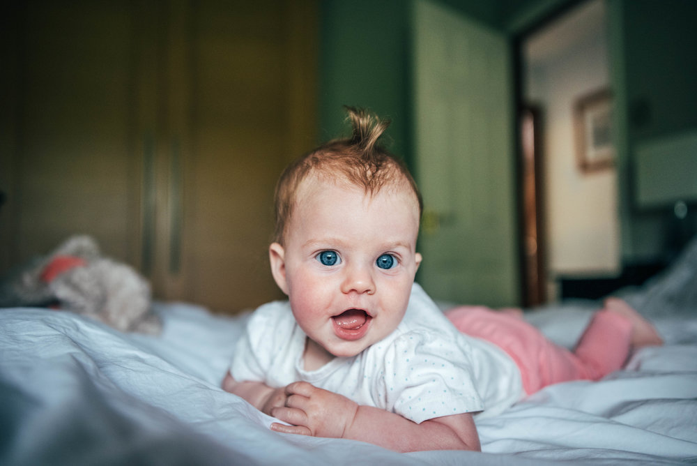 Baby Girl on bed at home Sessions Essex Documentary Portrait Photographer