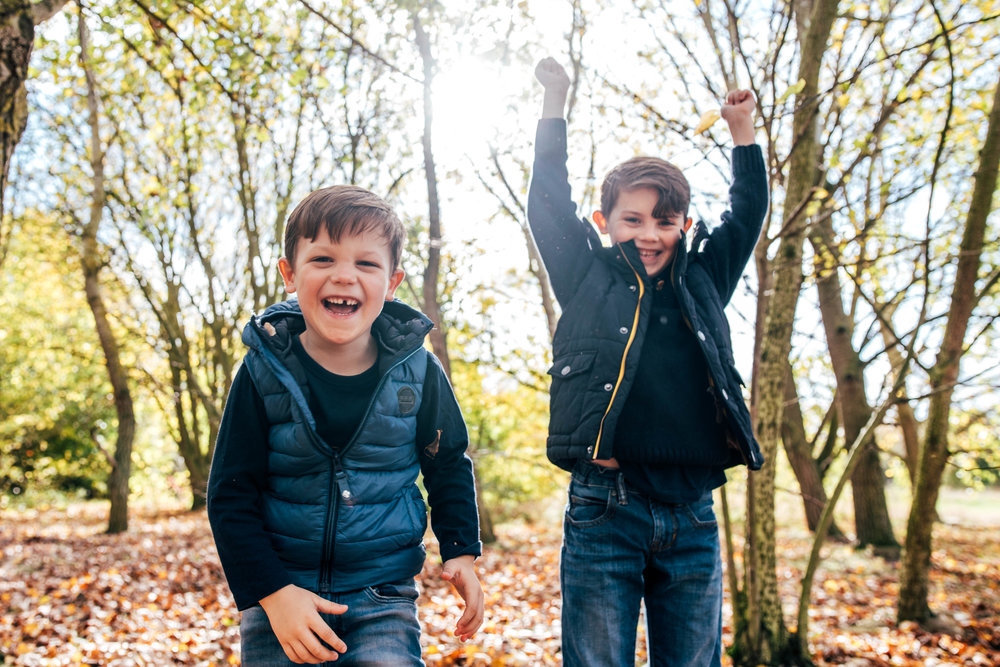 Two boys laugh in Autumn wood Essex Documentary Portrait Photographer