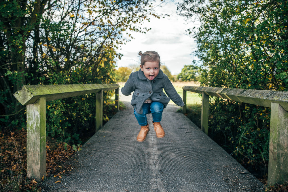 Little girl jumps on bridge Essex Documentary Portrait Photographer