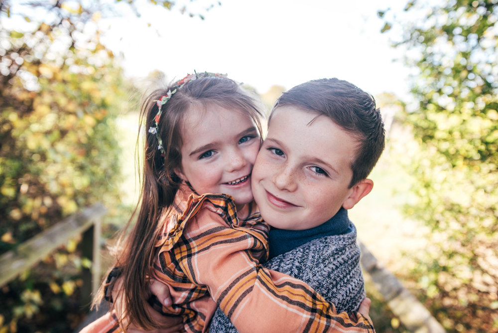 Brother and sister hug on bridge Essex Documentary Portrait Photographer