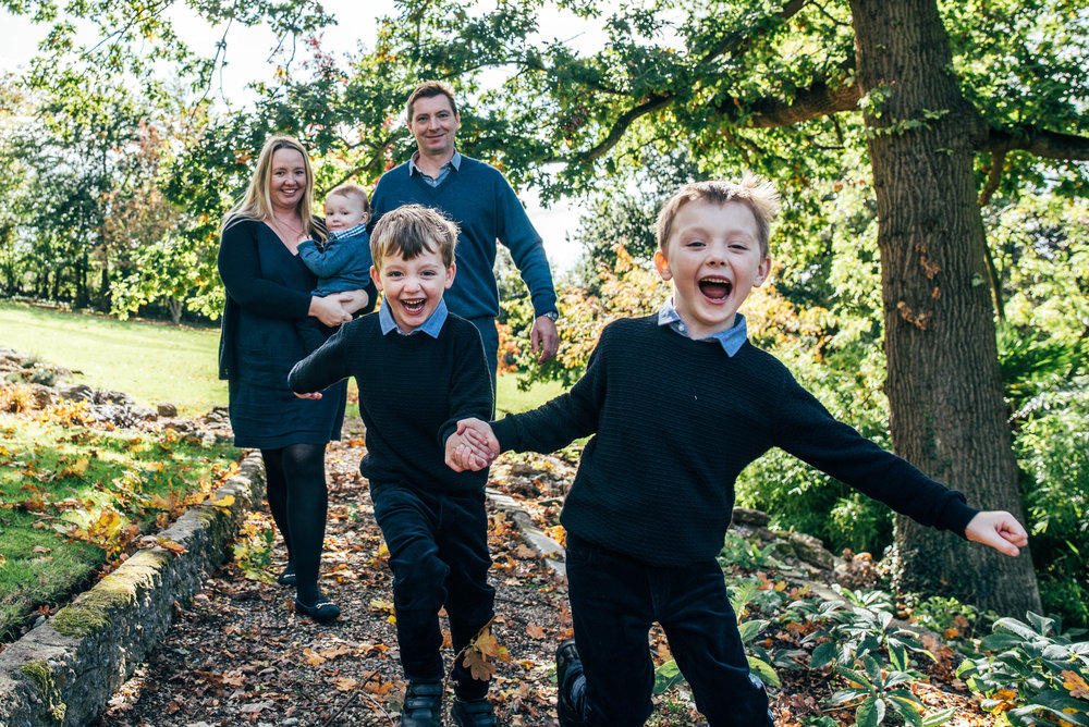 Boys run towards camera in garden Essex Documentary Portrait Photographer