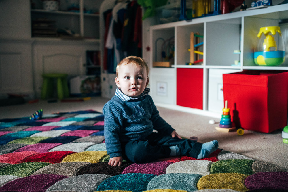 baby boy sits on playroom floor Essex Documentary Portrait Photographer