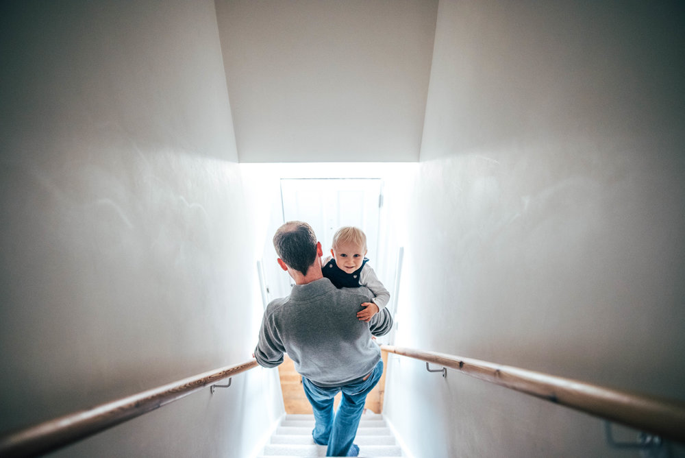 Dad walks down stairs with baby boy Essex Documentary Portrait Photographer