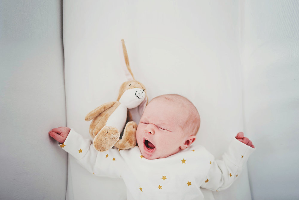 Newborn baby yawns in crib essex Documentary Portrait photographer