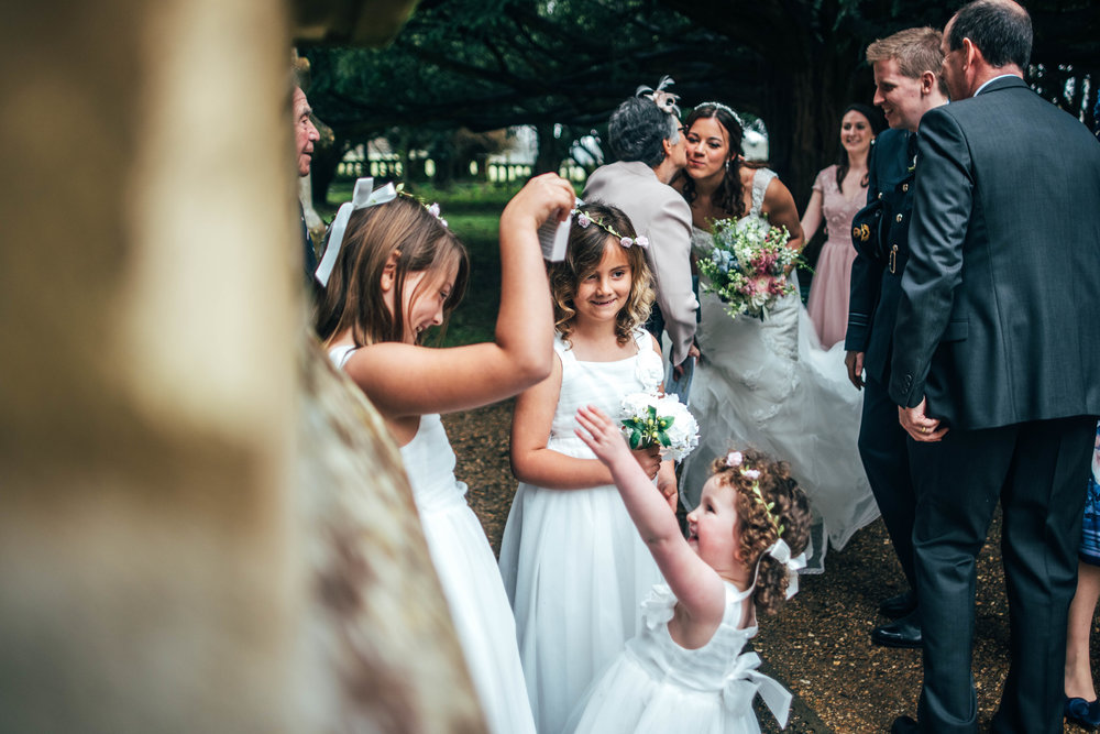 A Rustic DIY Spring Wedding St Nicholas' Church, Chawton & Chichester Hall, Witley. With trestle tables, wild flowers in bottles. Bride wears Pronovias. Essex Documentary Wedding Photographer