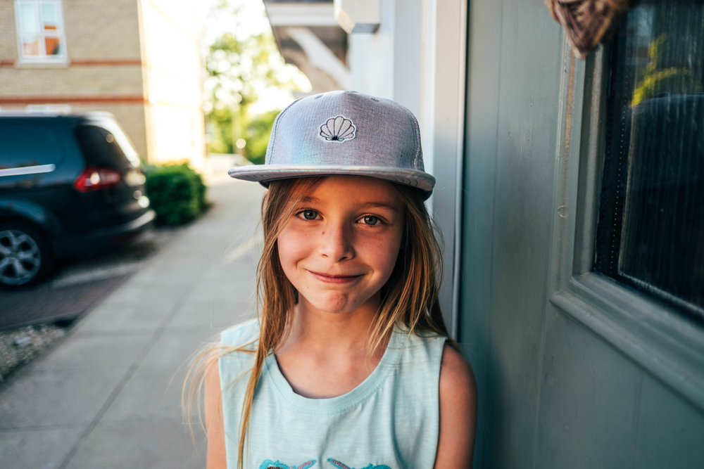 Little girl in cap smiles Essex Documentary Family and Wedding Photographer