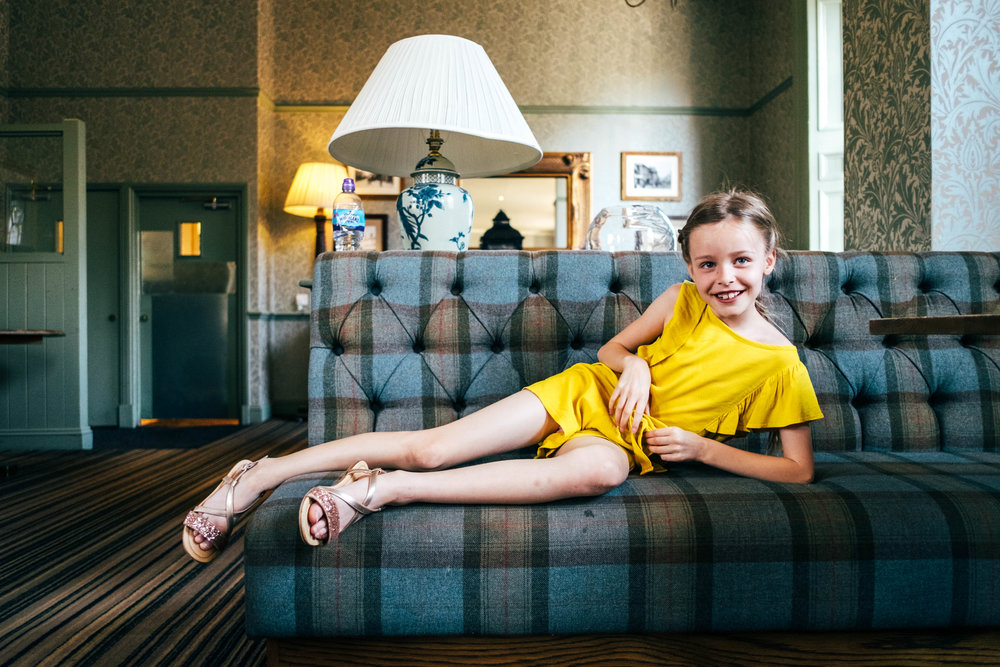 Little girl lazes on sofa in hotel Essex Documentary Family and Wedding Photographer