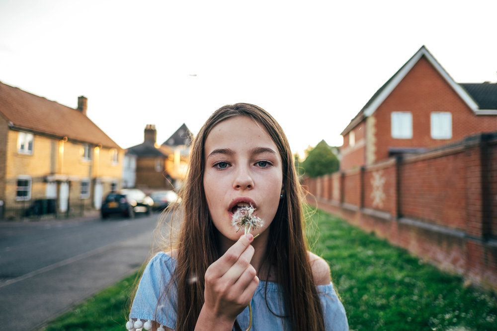 Tween girl blows dandelion Essex Documentary Wedding and Family Photographer