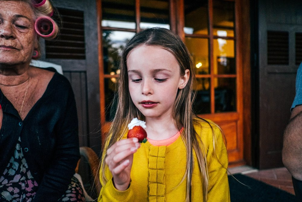 Little girl eats strawberry Essex Documentary Family Photographer
