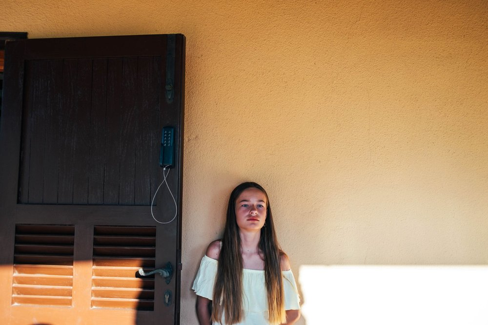 Tween girl in shade by villa in Tuscany Essex documentary travel family photographer
