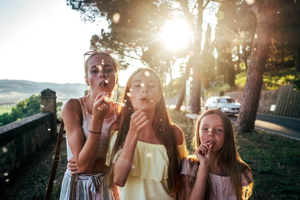 Three sisters blow dandelions in Tuscan sunset Essex Documentary Family Travel photographer