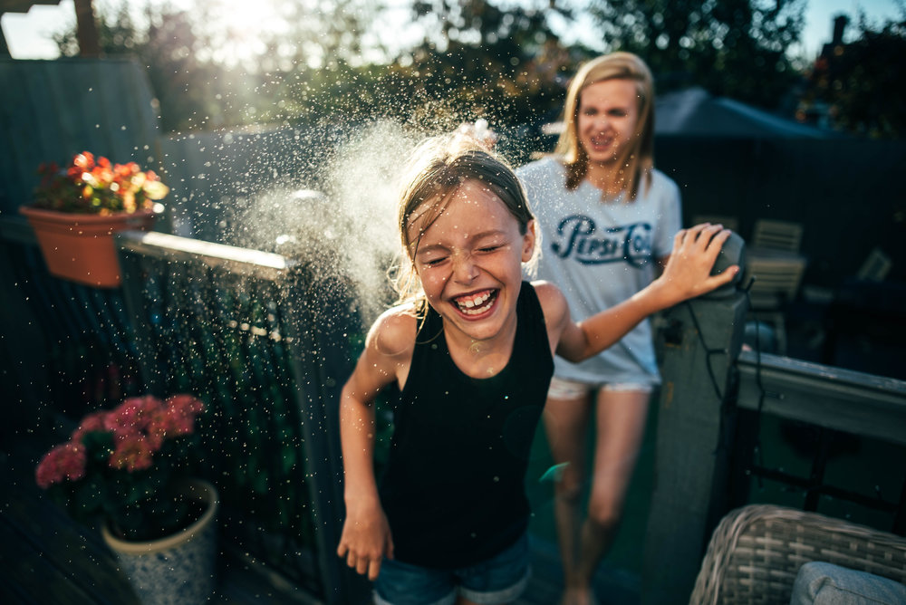 Young girl has water fight with sister at sunset Essex Documentary Family Wedding Photographer