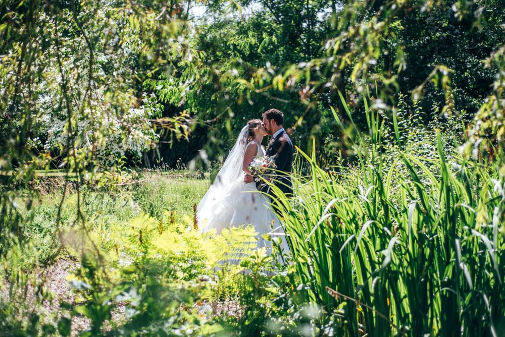 Rustic Summer wedding at Ratsbury Barn with Mini Golf, lawn games, pizza and home-made cake. Bride wears Mori Lee.  Essex Documentary Wedding Photographer