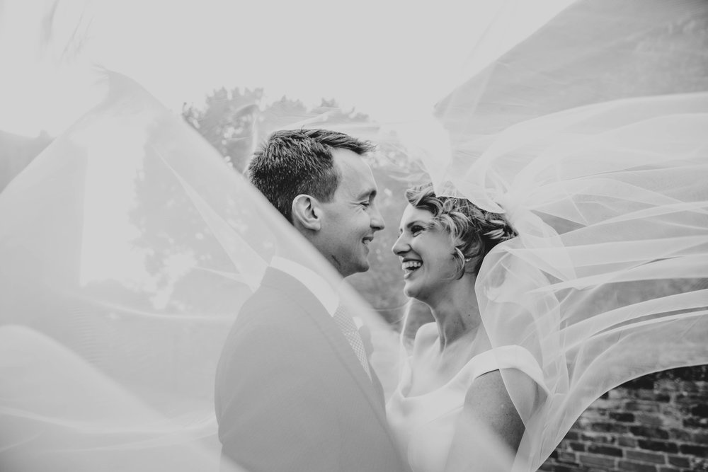 Bride & Groom laugh under windswept veil in Hedingham Castle Wedding Essex Documentary Wedding Photographer