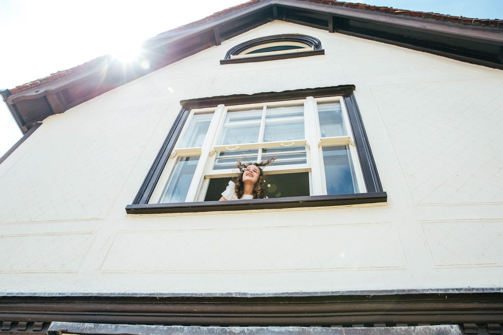Flower girl looks out of window Farm Wedding Essex Documentary Wedding Photographer