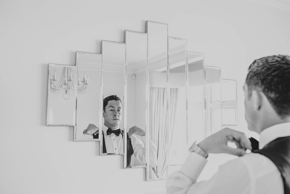Groom in Black tie in Mirror for Stock Brook Manor, Billericay.  Essex Documentary Wedding Photographer
