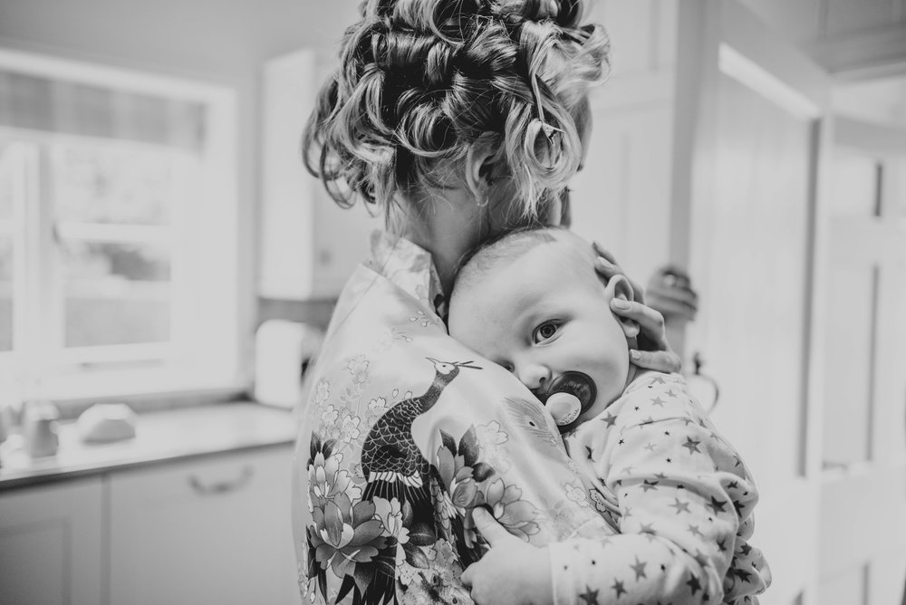Baby cuddles Bride at Blake Hall, Ongar, Essex Documentary Wedding Photographer