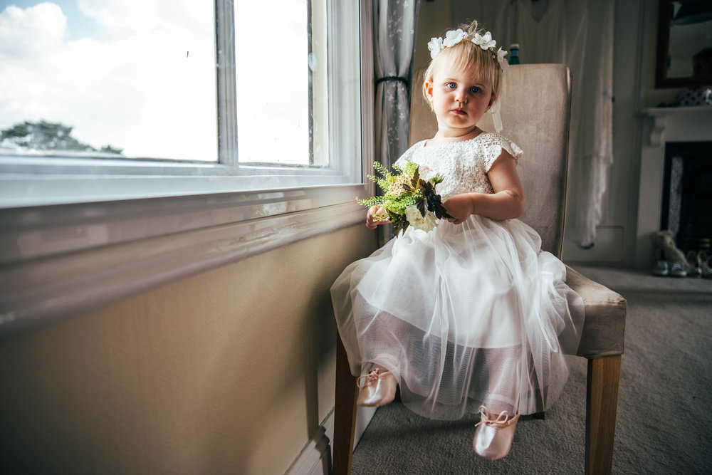 Flower Girl sits by window for Boho Farm Wedding Essex Documentary Wedding Photographer