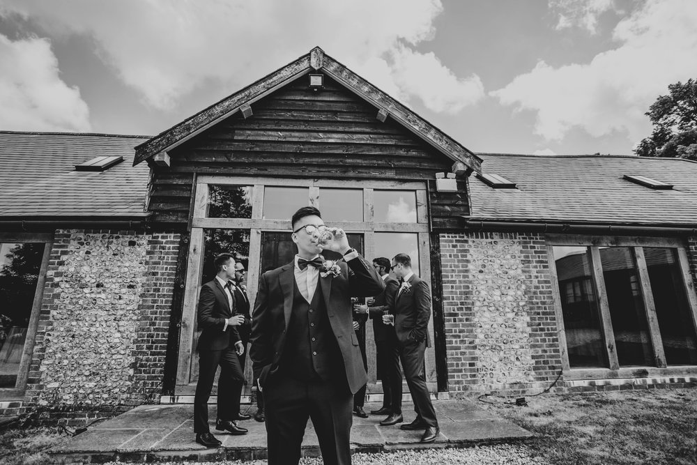 Groom and Groomsmen drink whiskey before ceremony at The Long Barn, Essex Documentary Wedding Photographer