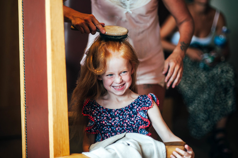 Flower girl smiles as her hair is brushed.  Stock Brook Manor, Billericay.  Essex Documentary Wedding Photographer