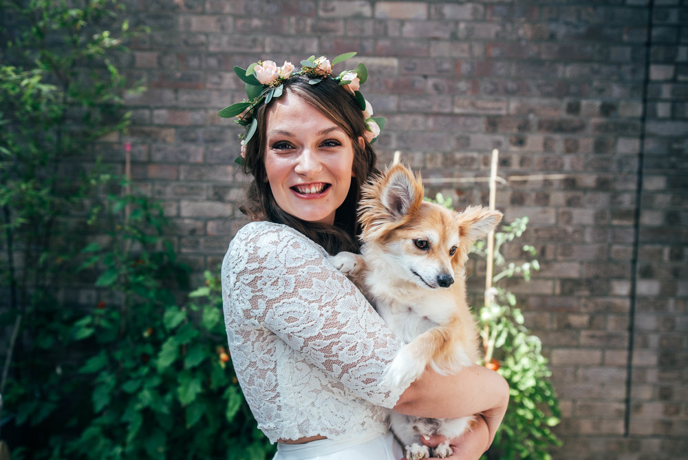 Boho Bride in Flower Crown holds puppy for Bedinghams Farm Wedding Essex Documentary Wedding Photographer