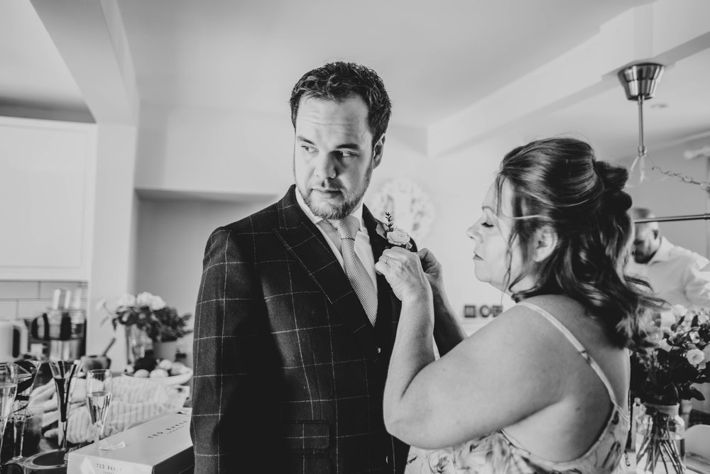 Grooms mum pins button hole on him for Ratsbury Barn Wedding.   Essex Documentary Wedding Photographer
