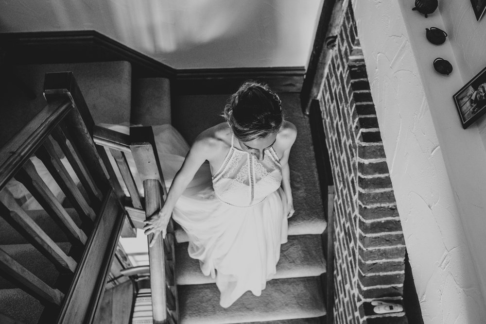 Bride walks downstairs to her  DIY Back Garden Tipi Wedding Essex Documentary Wedding Photographer