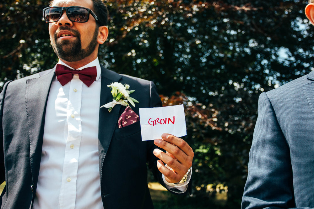 Usher holds card in pre-wedding game Essex Documentary Wedding Photographer
